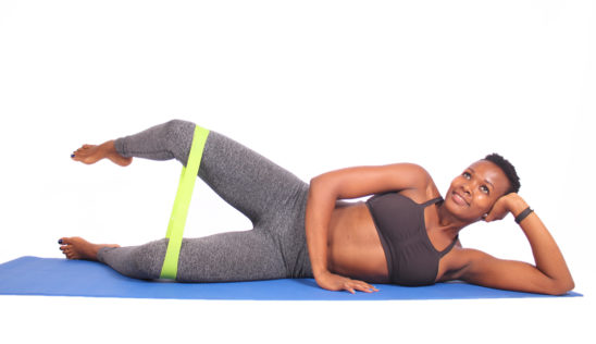 Smiling woman exercising with resistance band