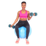 Smiling woman lifting dumbbells sitting on swiss ball