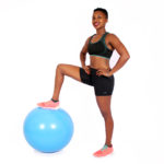 Smiling woman stepping on swiss ball with one leg