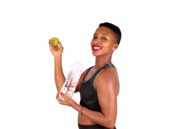 Smiling woman with apple and water