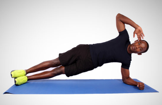 Sporty man doing side plank exercise