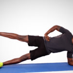Sporty man doing side plank with leg raised