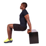 Sporty man doing triceps bench dips exercise