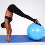 Sporty woman doing ab exercise with swiss ball