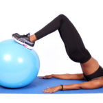 Sporty woman doing butt exercise on swiss ball
