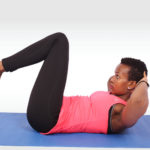 Sporty woman doing crunches while raising legs