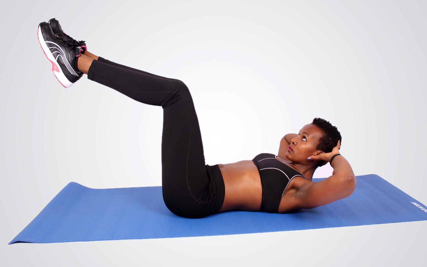 Sporty woman doing crunches with legs raised