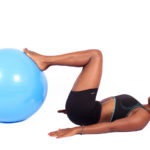 Sporty woman placing leg on swiss ball