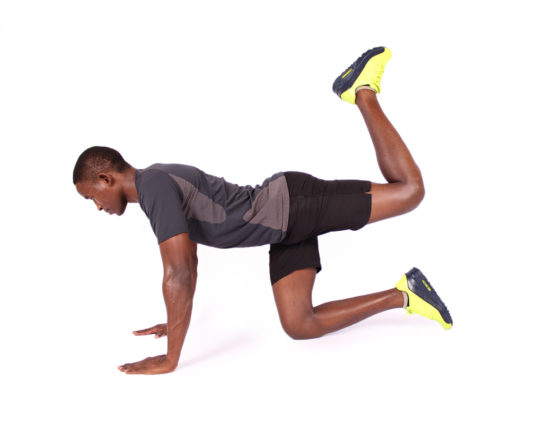 Sporty young man doing donkey kick exercise