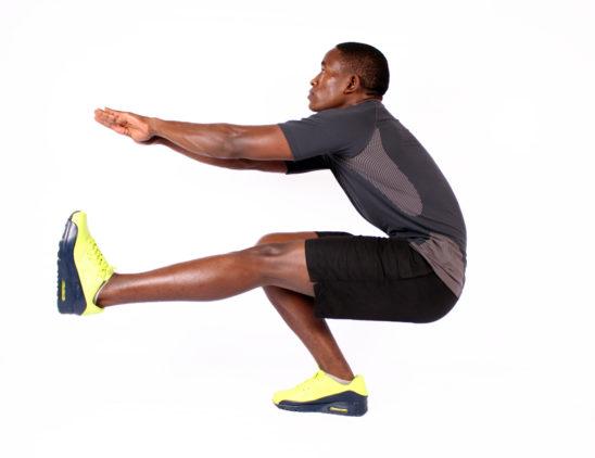 Strong man doing pistol squat exercise one leg squat