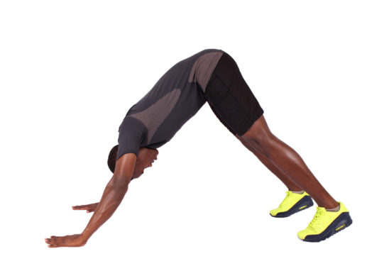 Strong man doing yoga pose and pike push ups