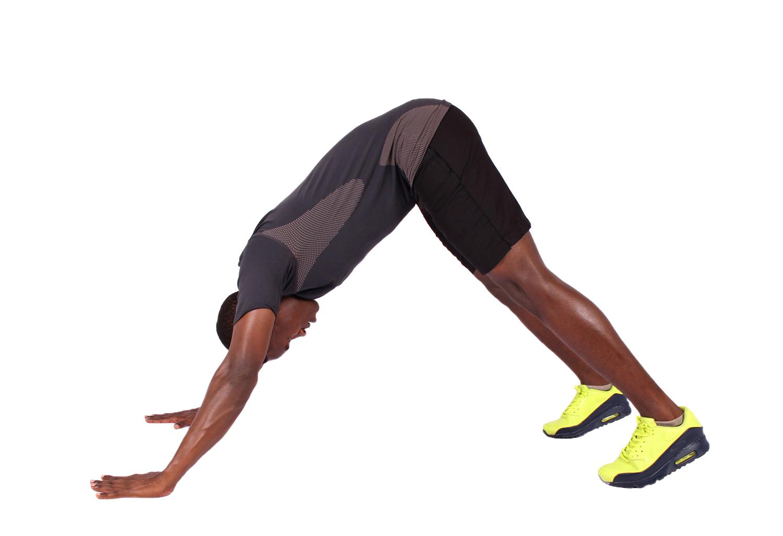 Strong man doing yoga pose and pike push ups