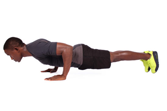 Strong muscular man doing push ups on isolated white background
