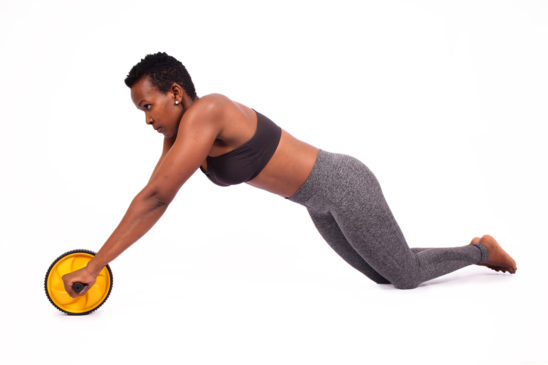 Strong woman doing ab wheel roller exercise kneeling