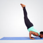 Strong woman doing chin stand yoga pose