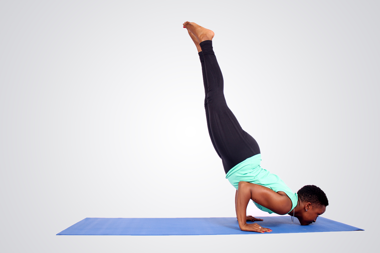 Strong woman doing chin stand yoga pose