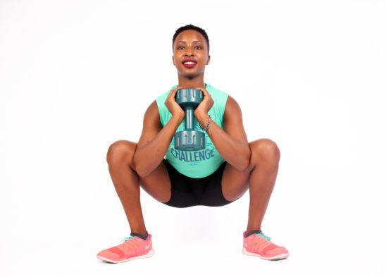 Strong woman doing deep squats with dumbbells