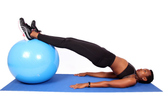 Strong woman doing lower back exercise with swiss ball