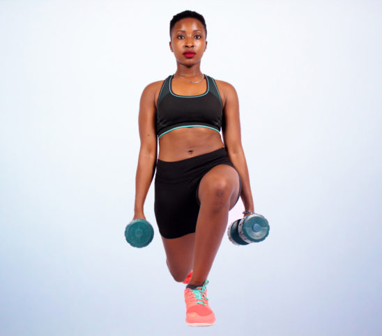 Strong woman doing lunges with dumbbells