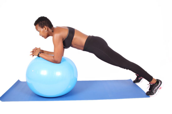 Strong woman doing plank on swiss ball