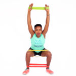 Strong woman doing squats with resistance band exercises