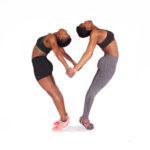 Two athletic females doing yoga