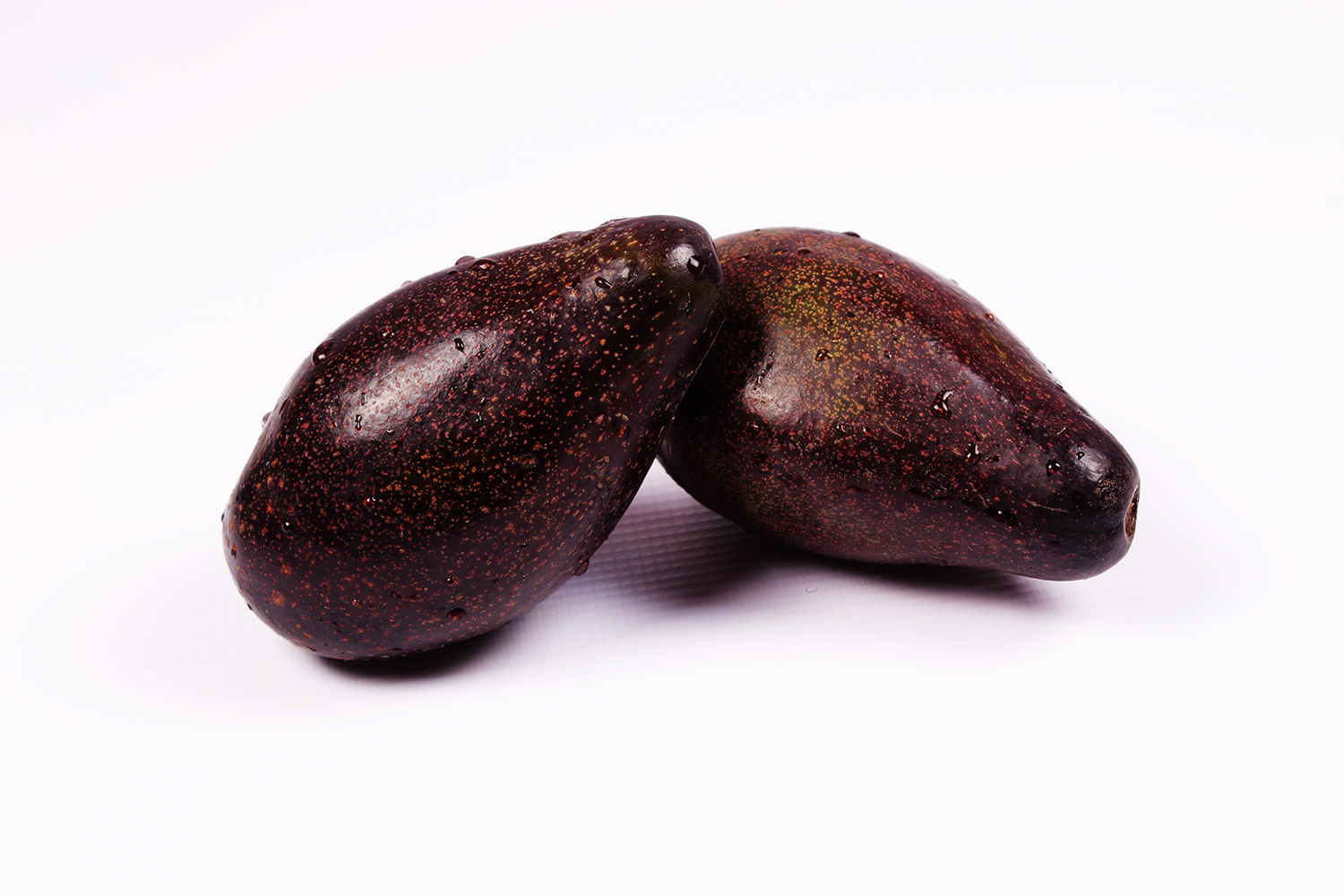 Two black avocados on isolated white background