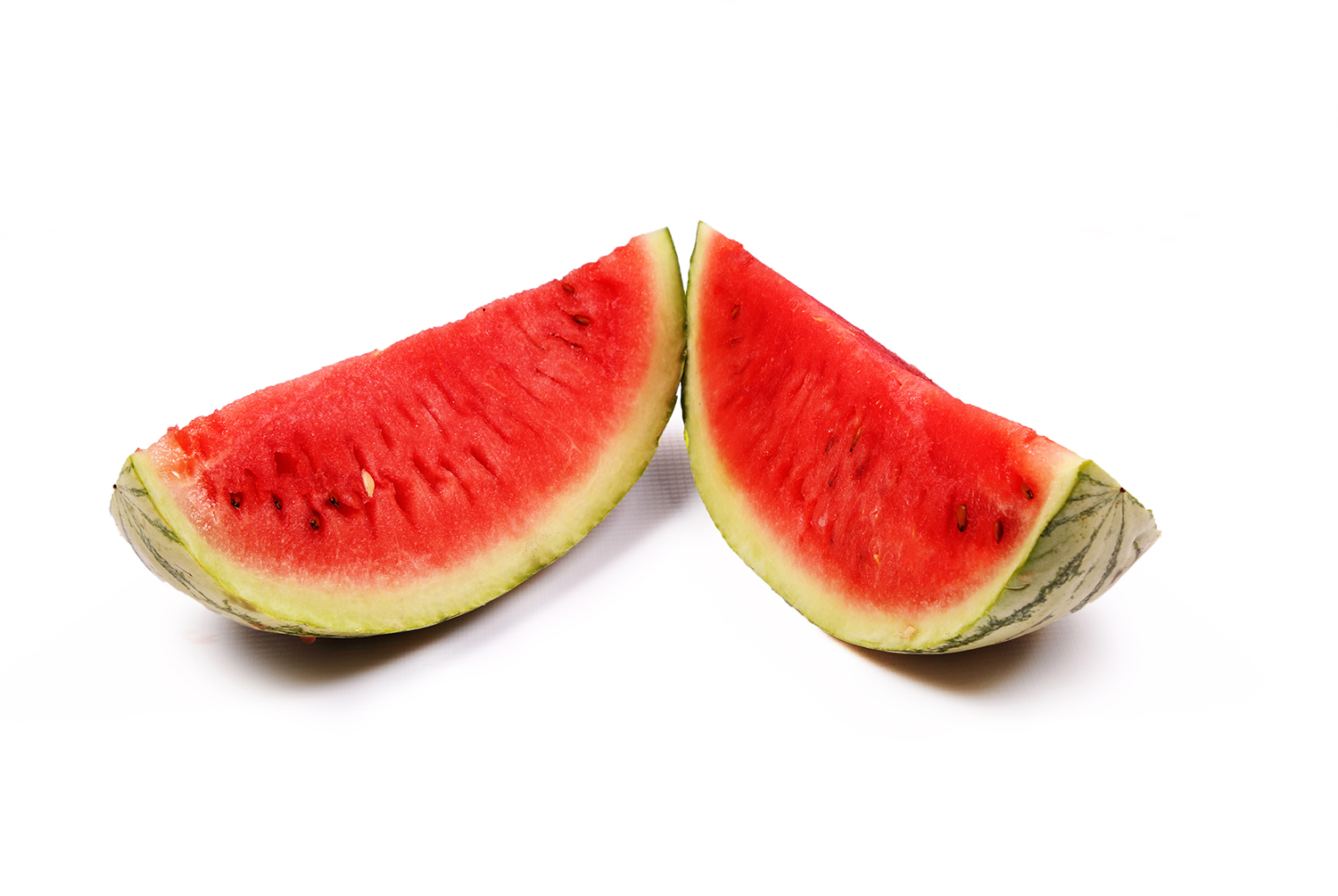 Two cut pieces of watermelon fruit on white background
