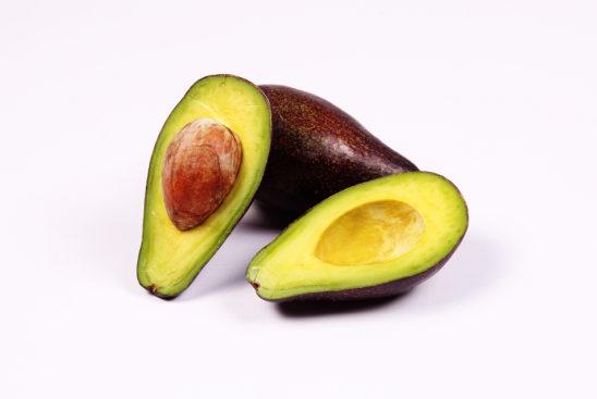 Two slices of avocado and one black avocado