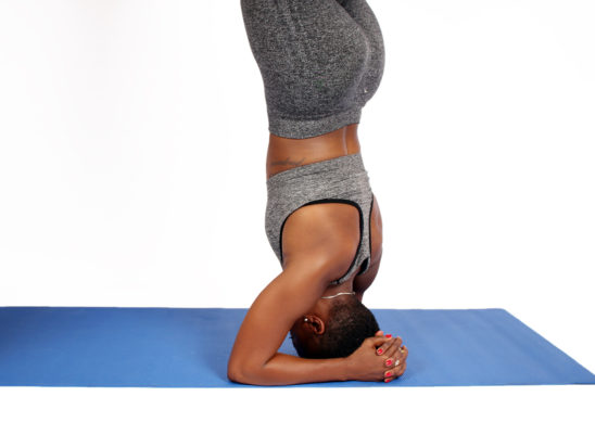 Upclose photo of woman doing headstand on yoga mat