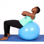 Woman doing crunches ab exercise on swiss ball