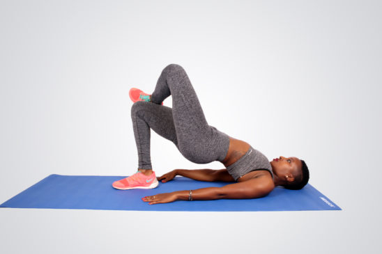 Woman doing four figure glute bridges