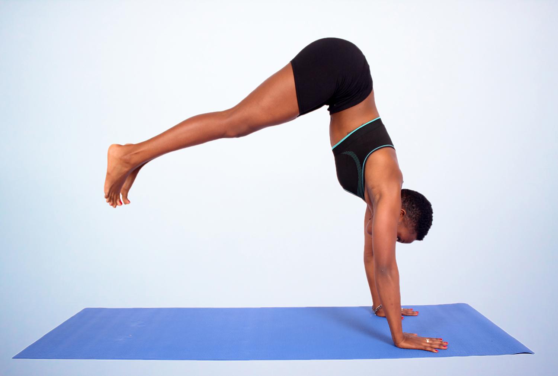 Woman Doing Beginner Handstand Yoga Pose On Yoga Mat