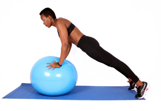 Woman doing push ups arm exercise on swiss ball