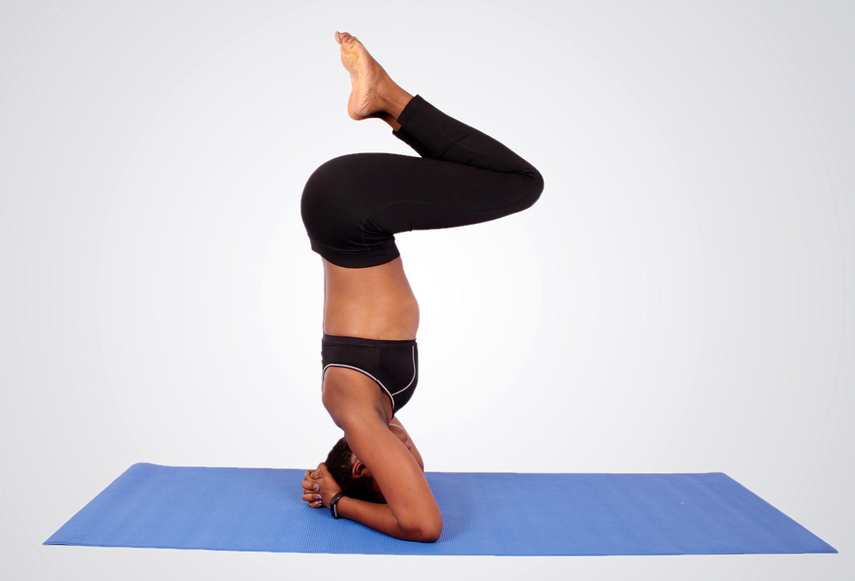 Woman doing yoga head stand pose