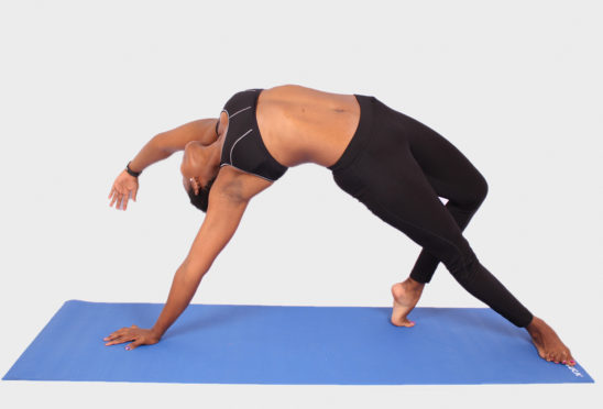 Woman doing yoga pose on blue yoga mat