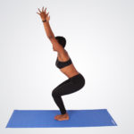 Woman doing yoga pose while squatting