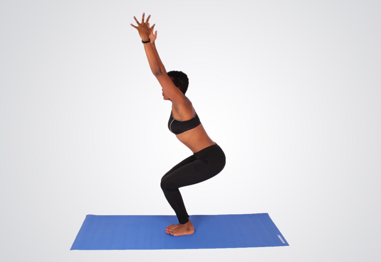 Woman doing yoga pose while squatting