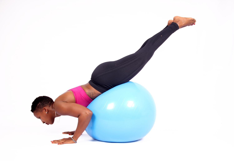 Woman exercising on swiss ball legs raised