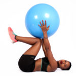 Woman with sportswear lifts swiss ball