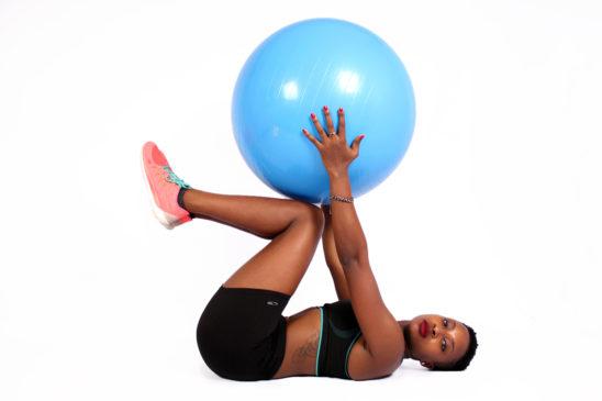 Woman with sportswear lifts swiss ball
