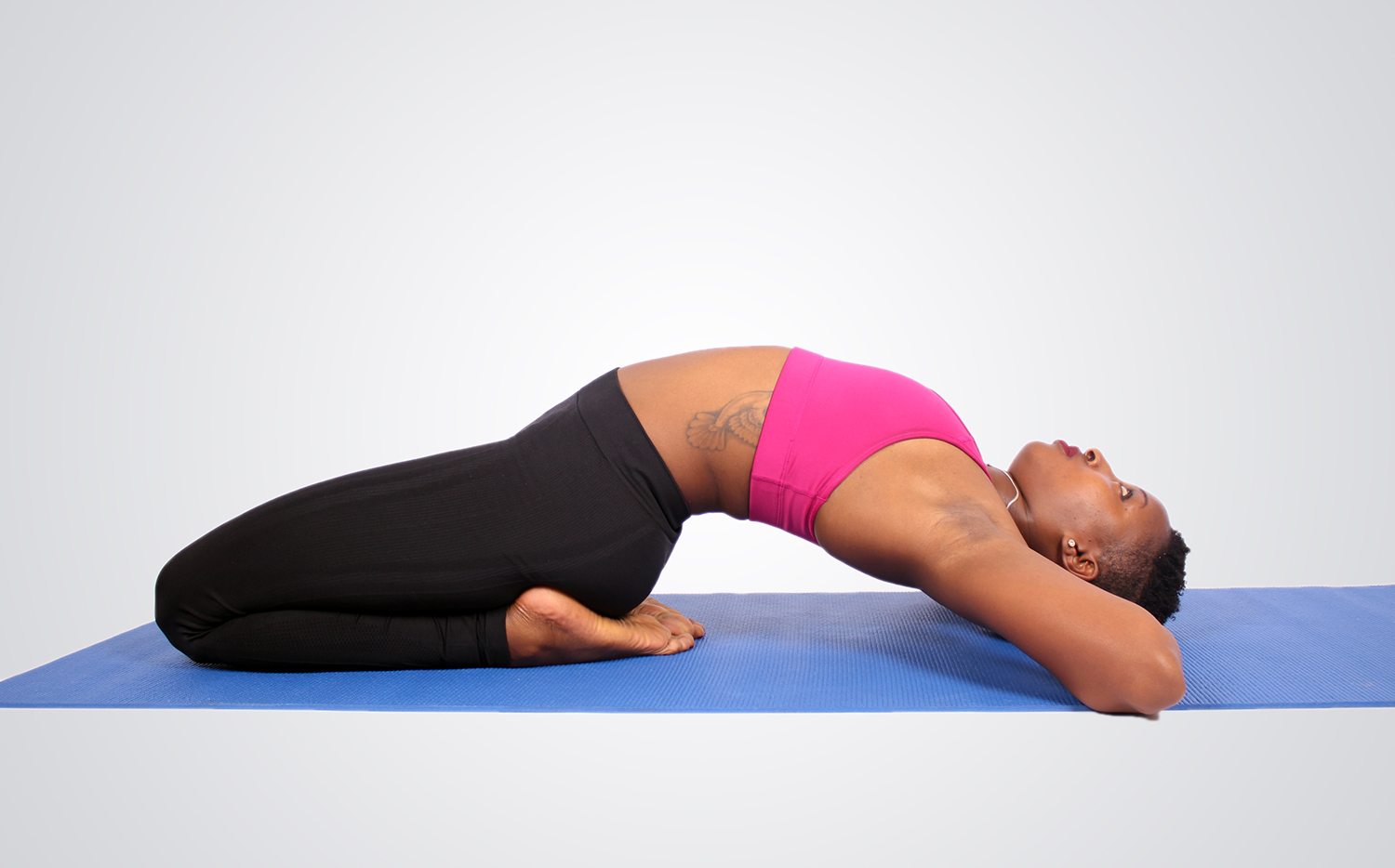 Woman with tattoo practicing yoga