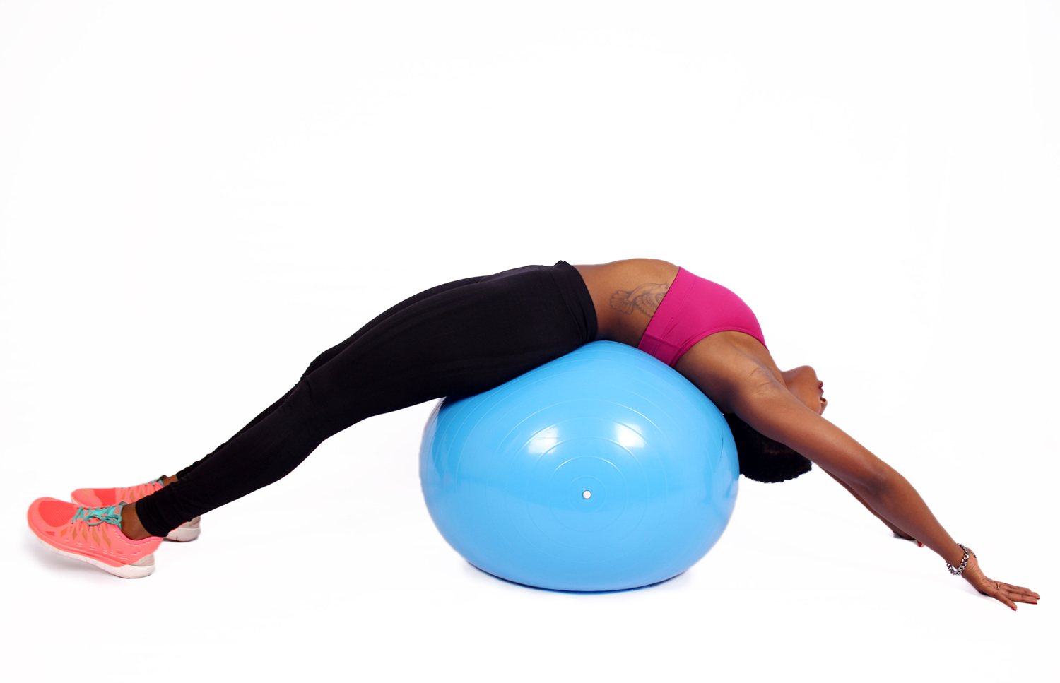 Woman with tattoo stretching on swiss ball