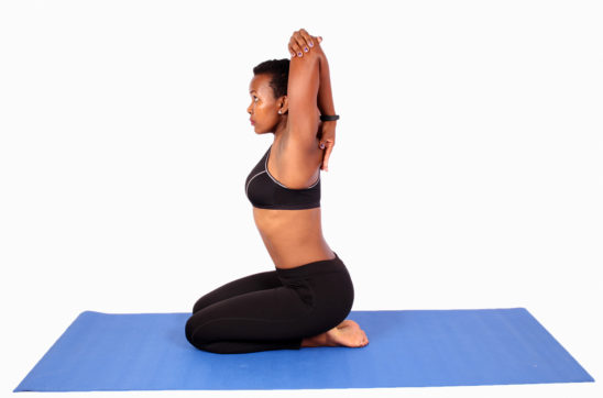 Yogi stretching shoulders and triceps on yoga mat