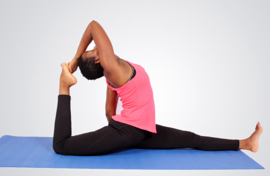 Young african woman doing yoga on yoga mat