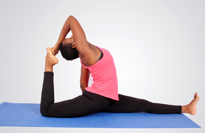 Young african woman doing yoga on yoga mat