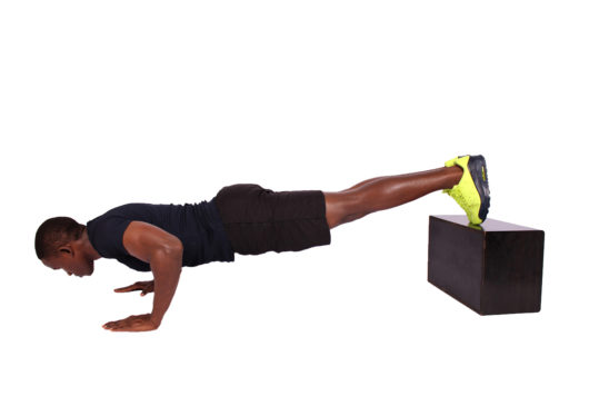 Young athletic man doing decline push ups legs raised