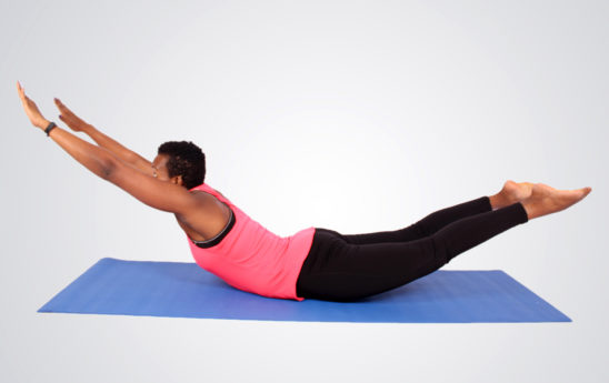 Young fit woman doing superman lower back exercise