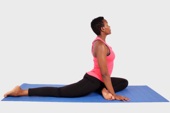 Young fit woman doing yoga on isolated background