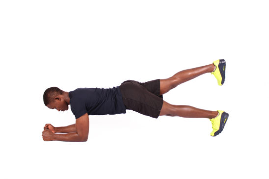 Young man doing front plank raising one leg